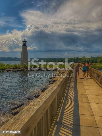 177362898istockphoto Beautiful view of light house and Lake Michigan and clouds from a wooden walkway with three females , a family, that are walking in the distance . 1128154483