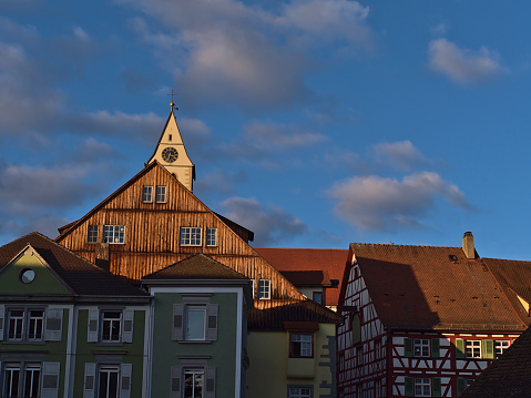 Beautiful view of old buildings in the historic center of Meersburg, Lake Constance, Germany with half-timbered house, colorful facades, tiled roofs and church steeple in afternoon light.