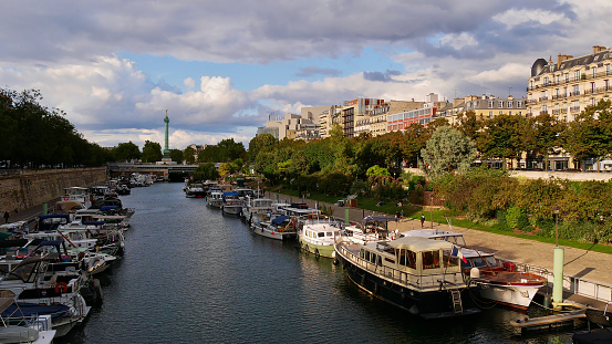 Beautiful view of peaceful Canal Saint-Martin with docking boats, people walking on the promenade and famous July Column located on Place de la Bastille.