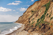 Beautiful view of sandy cliff near sea beach. Landscape of beach cliff and waves. Summer vacation concept. Exploring interesting places