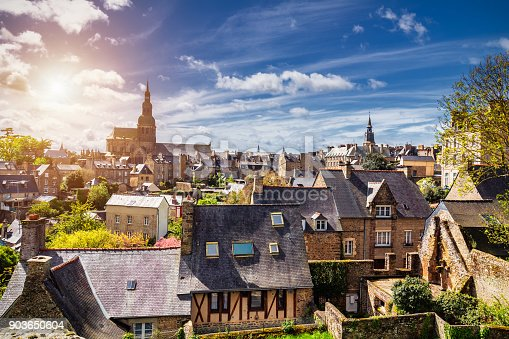 istock Beautiful view of scenic narrow alley with historic traditional houses and cobbled street in an old town of Dinan with blue sky and clouds. Brittany (Bretagne), France 903650604
