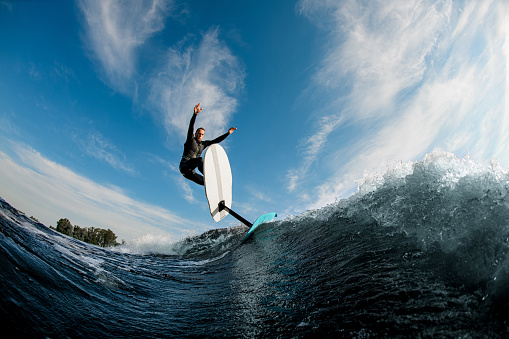 Beautiful view of sportive man riding on the wave with hydrofoil foilboard