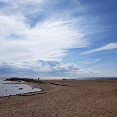 Beautiful view of the pier, sandy beach, water, sky with a pattern of clouds