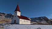 istock Beautiful view of the small church of village Vík í Mýrdal located on the southern coast of Iceland with white wall and red colored roof on sunny winter day with rugged mountains. 1313276513