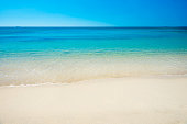 Beautiful horizon view of tropical sea and sand beach under blue sky