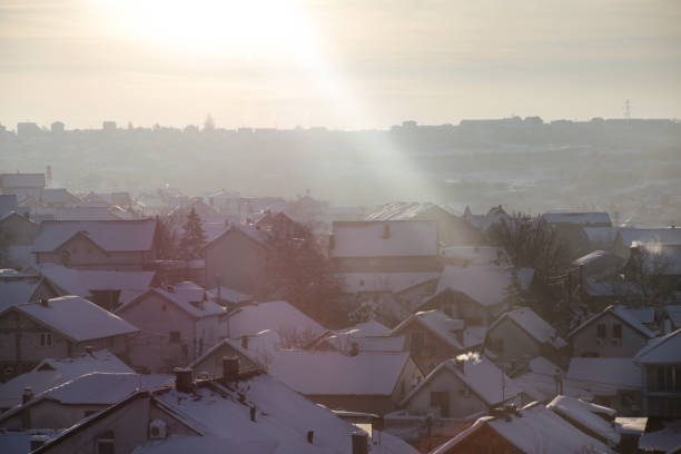 Beautiful view of winter morning fog, snow and sun filling on landscape of houses and buildings in Belgrade. Scenery during sunrise, sunset of top view at settlement is very popular for photographer. stock photo