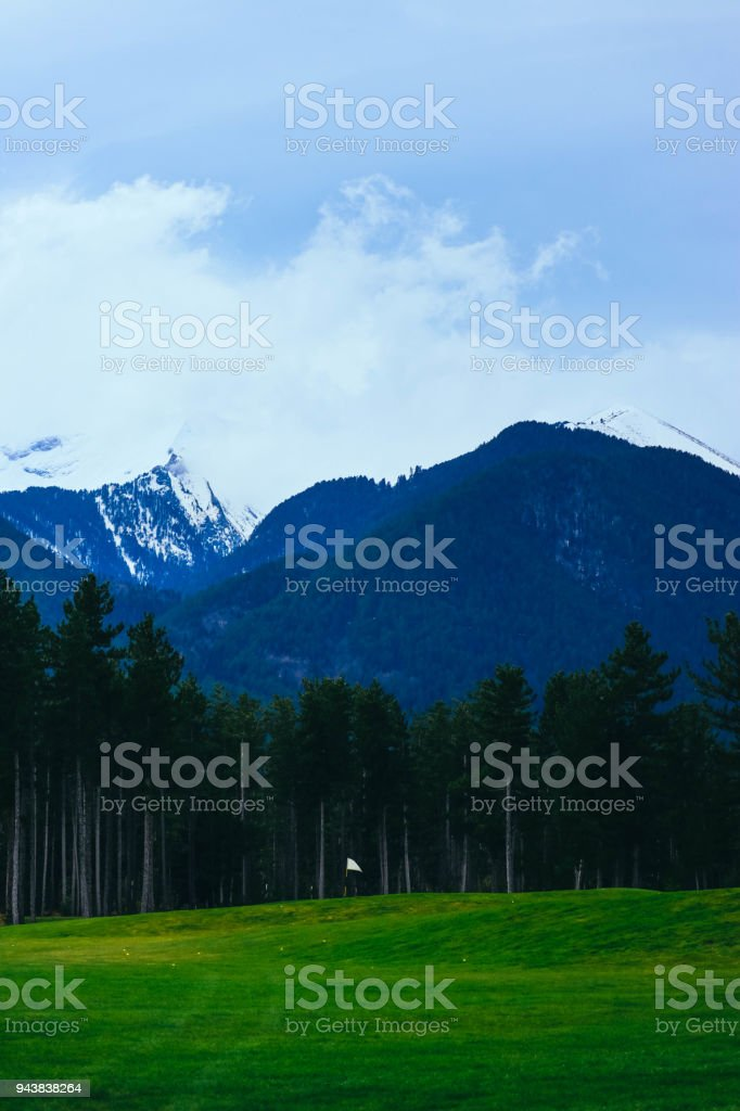 Beautiful view on the high mountains ice peaks, pine forest and golf course. stock photo