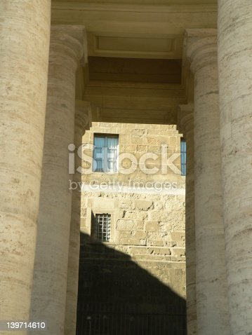 a glimps of a window in the vatican city surrounded with pillars