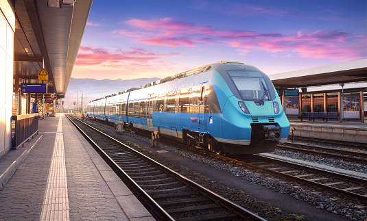 Beautiful view with modern commuter train on the railway station and colorful sky with clouds at sunset in Europe. Industrial landscape with blue train on railway platform. Railroad background