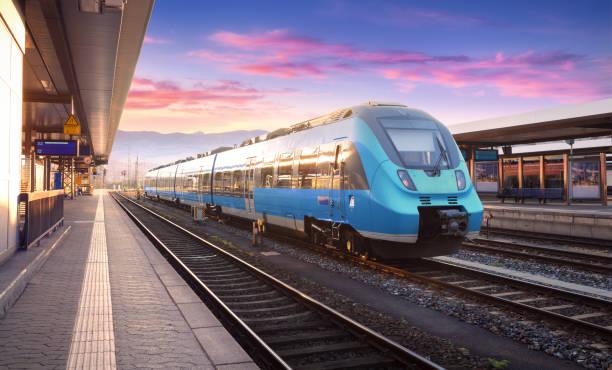 Bela vista com moderno trem na estação de comboios e colorido céu com nuvens ao pôr do sol na Europa. Paisagem industrial com trem azul na plataforma ferroviária. Fundo de ferrovia - foto de acervo