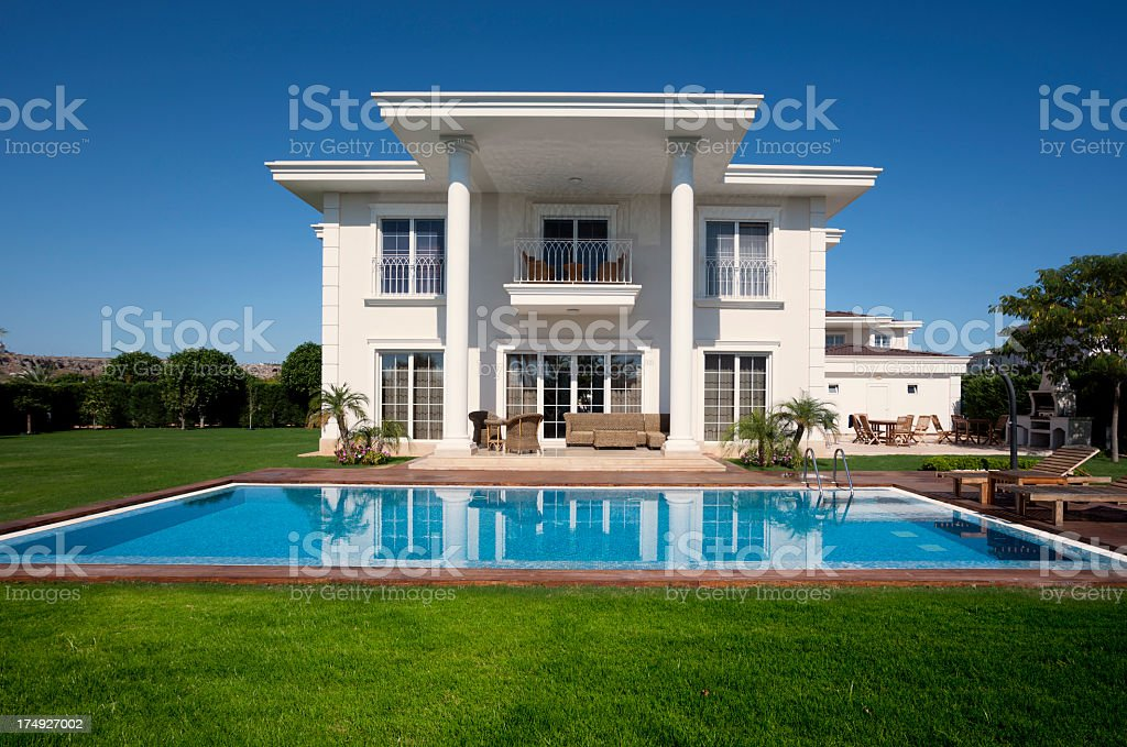 Beautiful villa house overlooking pool with manicured lawn stock photo