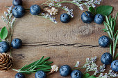 Beautiful vintage background or wallpaper frame of fresh wild blueberries on wood plank in top view flat lay with copy space. Blueberry is antioxidant food and have vitamin C. Healthy fruits concept.