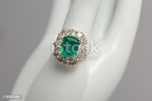 A shiny green emerald gemstone surrounded by diamonds on a silver ring retail display close up