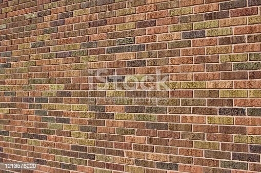 This images background shows a beautiful vintage textured brick wall with a patchwork quilt pattern in colorful earth tones.