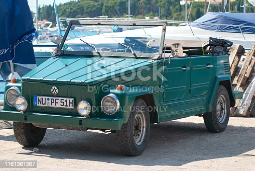 Beautiful vintage Volkswagen 181 (Thing) car on the pier with yahts and boats in the background, Adriatic Sea