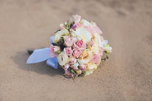 Beautiful vintage wedding bouquet flowers roses on sand beach