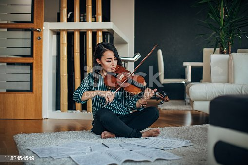 Young woman violinist practicing at home