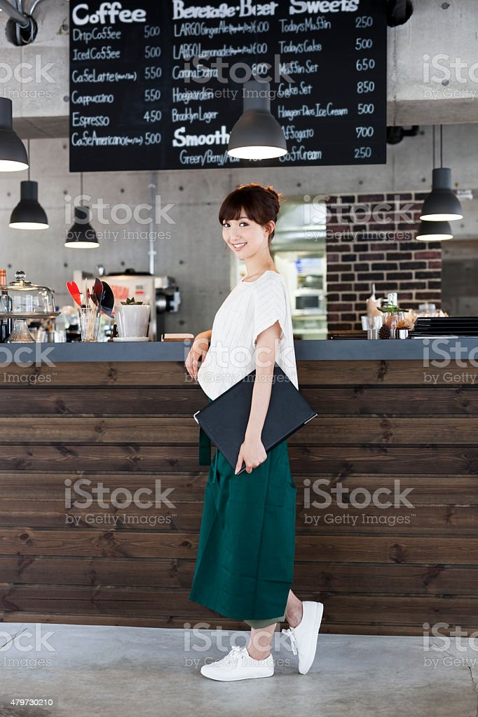 Beautiful waitress in front of a counter stock photo