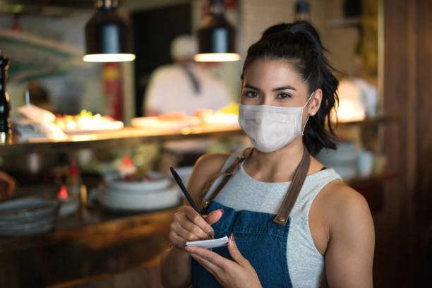 Schöne Kellnerin arbeitet in einem Restaurant mit einer Gesichtsmaske – Foto