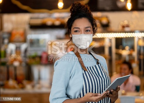 Portrait of a beautiful waitress working at a restaurant wearing a facemask to avoid the spread of coronavirus– COVID-19 lifestyle concepts