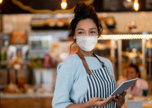 Beautiful waitress working at a restaurant wearing a facemask Portrait of a beautiful waitress working at a restaurant wearing a facemask to avoid the spread of coronavirus– COVID-19 lifestyle concepts restaurants stock pictures, royalty-free photos & images