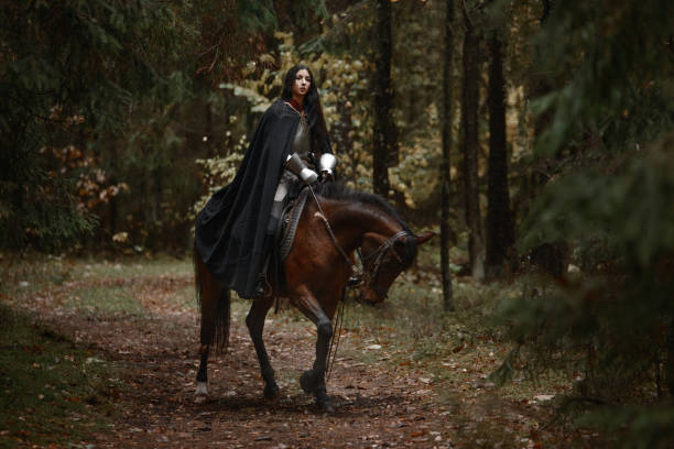 a beautiful warrior girl with a sword wearing chainmail and armor riding a horse in a mysterious forest. - knight on horse stock photos and pictures