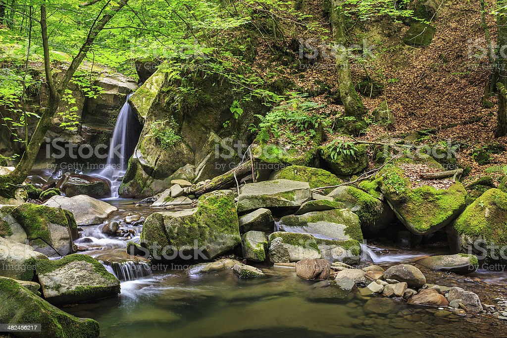 beautiful waterfall comes out of huge rock in the forest royalty-free stock photo