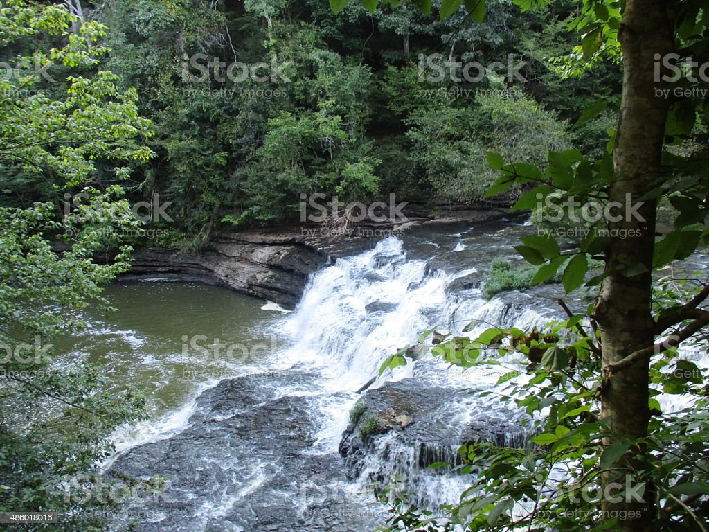 Beautiful Waterfall Nearly Surrounded by Trees and Rocks stock photo