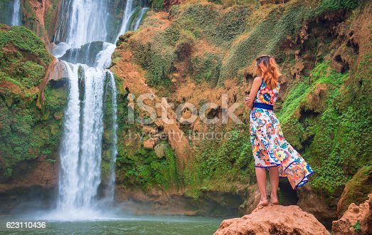 istock Beautiful waterfall of Morocco. Back woman in long dress looking 623110436