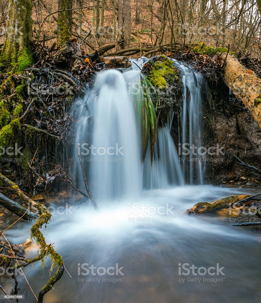 Beautiful waterfalls in the woods on cold autumn day stock photo