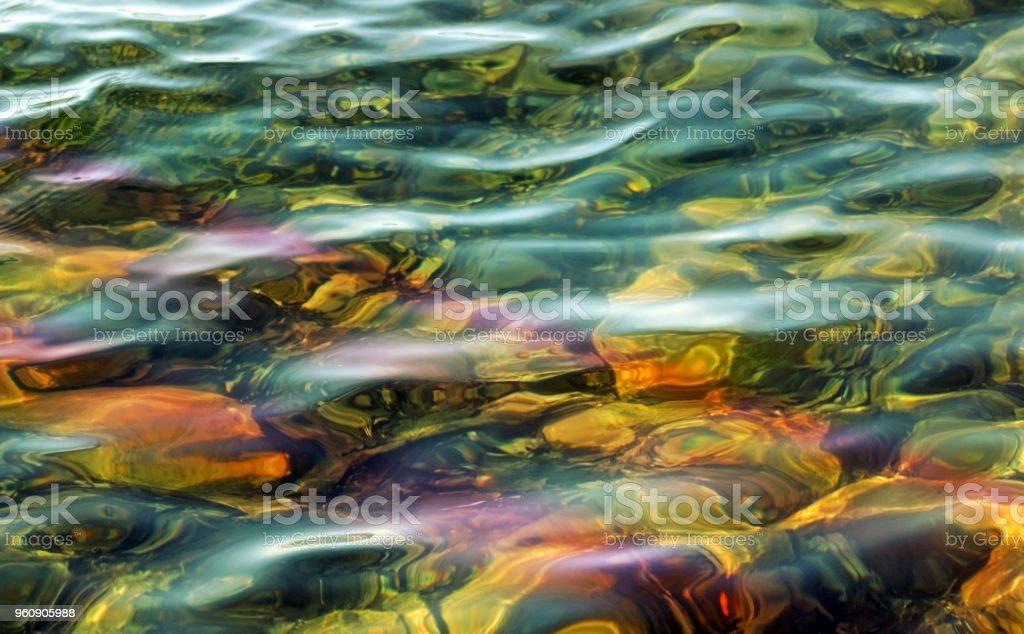 Schönen Gewässern mit weichen Wellen entlang der Oberfläche bewegt.   Felsen auf flachen Boden unten zu sehen - Lizenzfrei Bewegung Stock-Foto