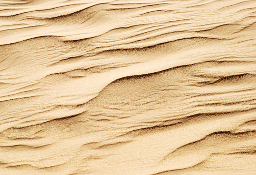Wind formed beautiful temporary sand pattern in the desert. The sand looks like frozen waves.