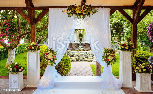 istock Beautiful wedding arch for the ceremony in the garden in sunny weather. 820380418