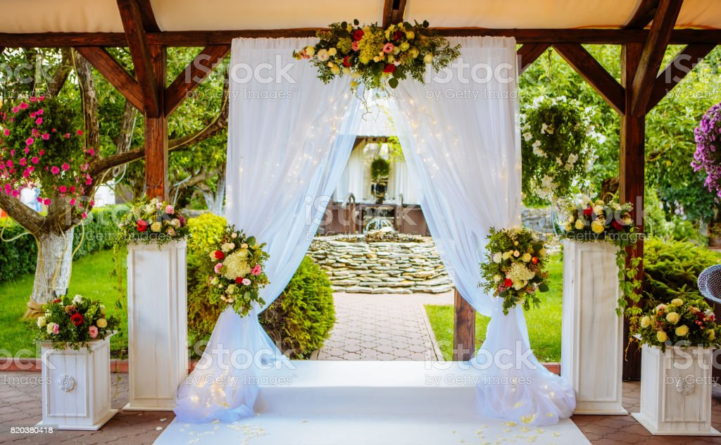 Beautiful wedding arch for the ceremony in the garden in sunny weather. stock photo