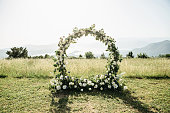 Beautiful wedding arch of flowers or white roses in a field or meadow. Preparation for a wedding event.