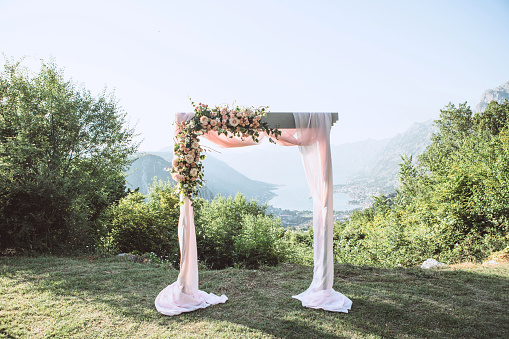 Beautiful wedding arch with flowers on the background of the Boko-Kotor Bay in Montenegro. Preparation for a wedding event.