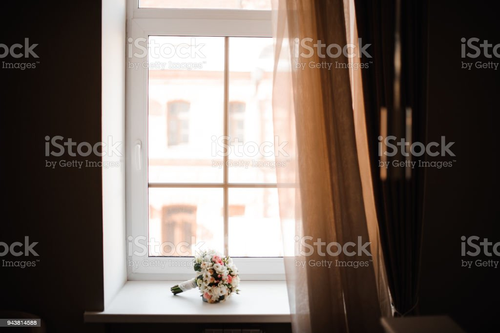 Beautiful and pretty wedding bouquet of flowers on the white window...