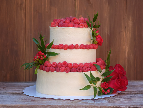beautiful wedding cake with red rose and fresh raspberries