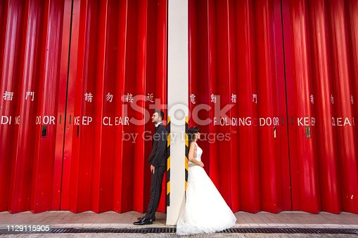 Beautiful wedding couple posing in front of red wall
