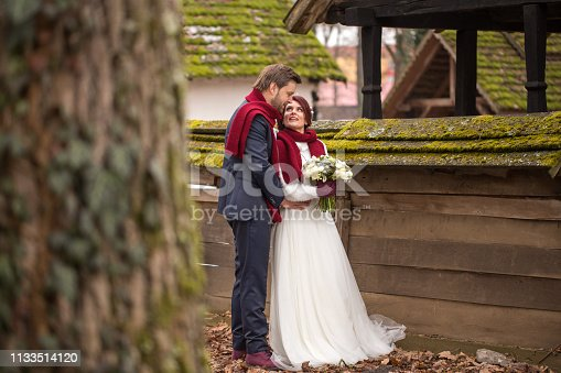 Beautiful wedding couple posing near old houses in village