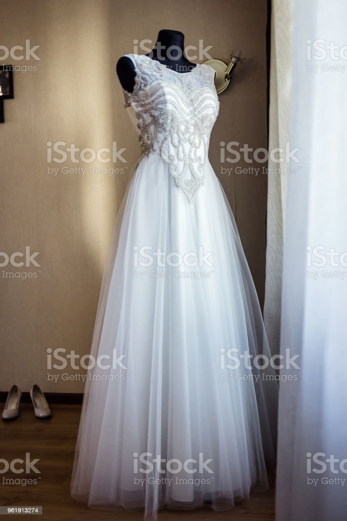 beautiful wedding dress hanging in the room, woman getting ready before  ceremony stock photo