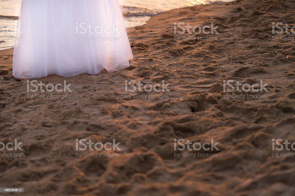 Beautiful wedding dress on sandy beach stock photo