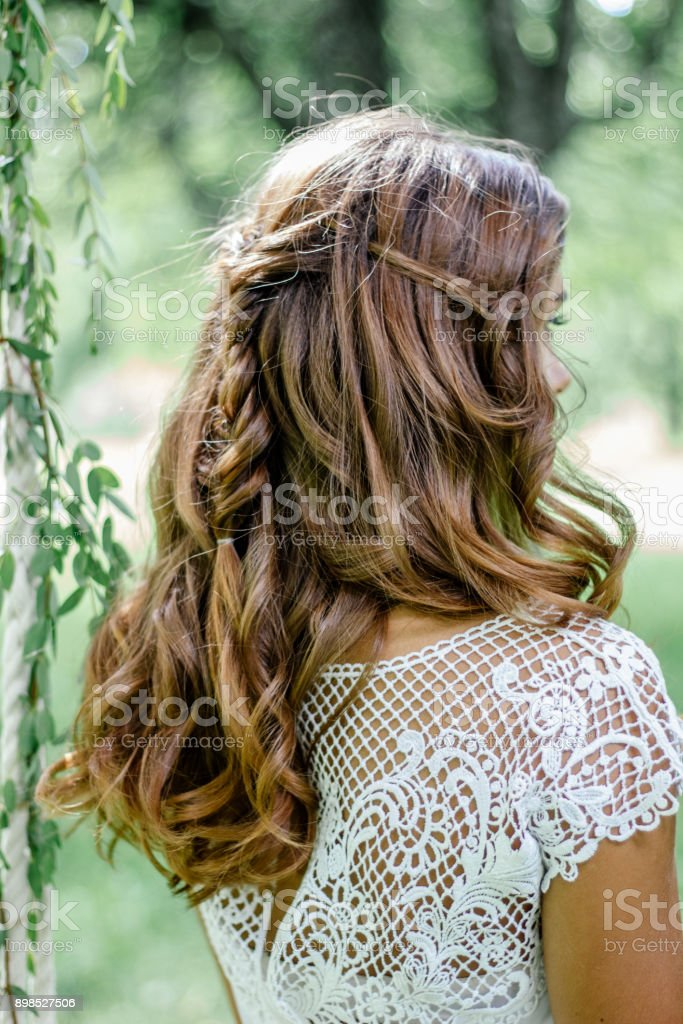 Beautiful wedding hairstyle with the bride turning back. stock photo
