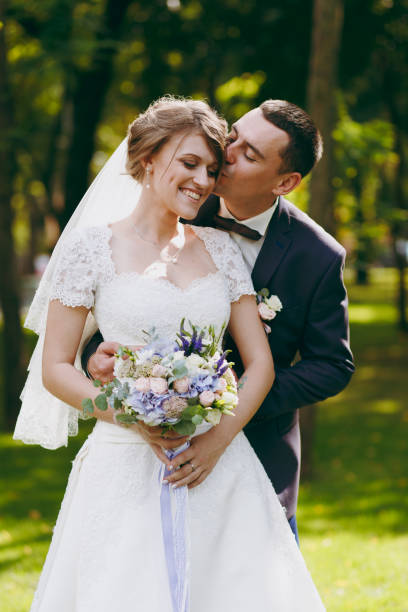 beautiful wedding photosession. handsome groom in blue formal suit and his elegant bride in dress and veil with bouquet with beautiful hairdress embrace on a walk in the big green park on sunny day - foto di matrimonio foto e immagini stock