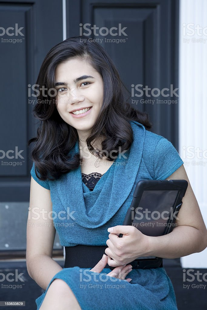 Beautiful, well dressed, young woman holding computer tablet stock photo
