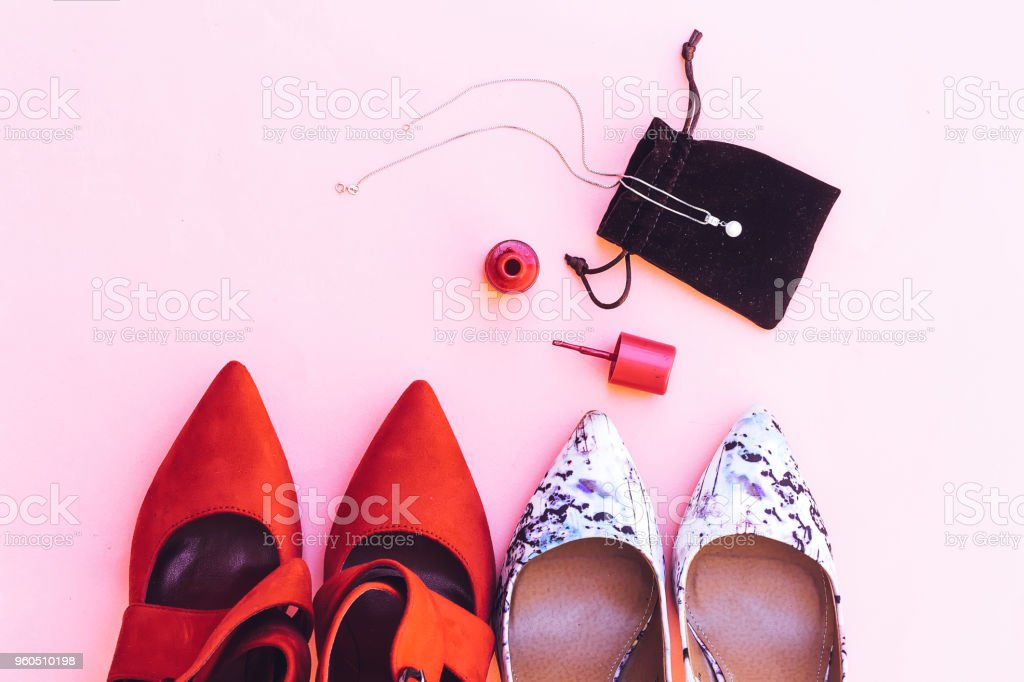beautiful white and red pump hight heeled and pink nail polish bottle and white pearl necklace stock photo