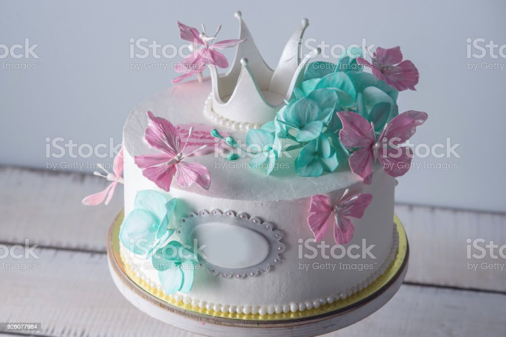 Beautiful white cake decorated with pink and turquoise flowers and a beautiful white cake decorated with pink and turquoise flowers and a princess crown concept of mightylinksfo