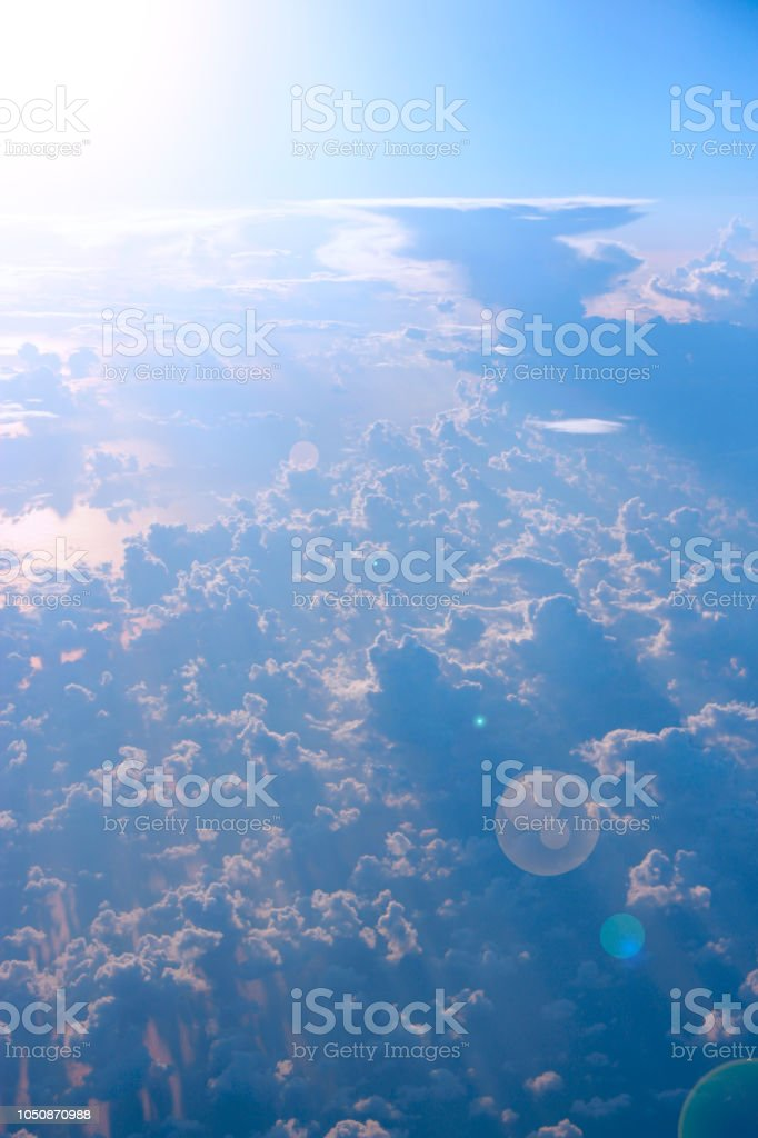 Wonderful view from window of plane to sun shining over clouds....