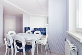 Beautiful white dining area with massive dining table and chairs for six with window and blue furniture. Light home relaxation interior concept.