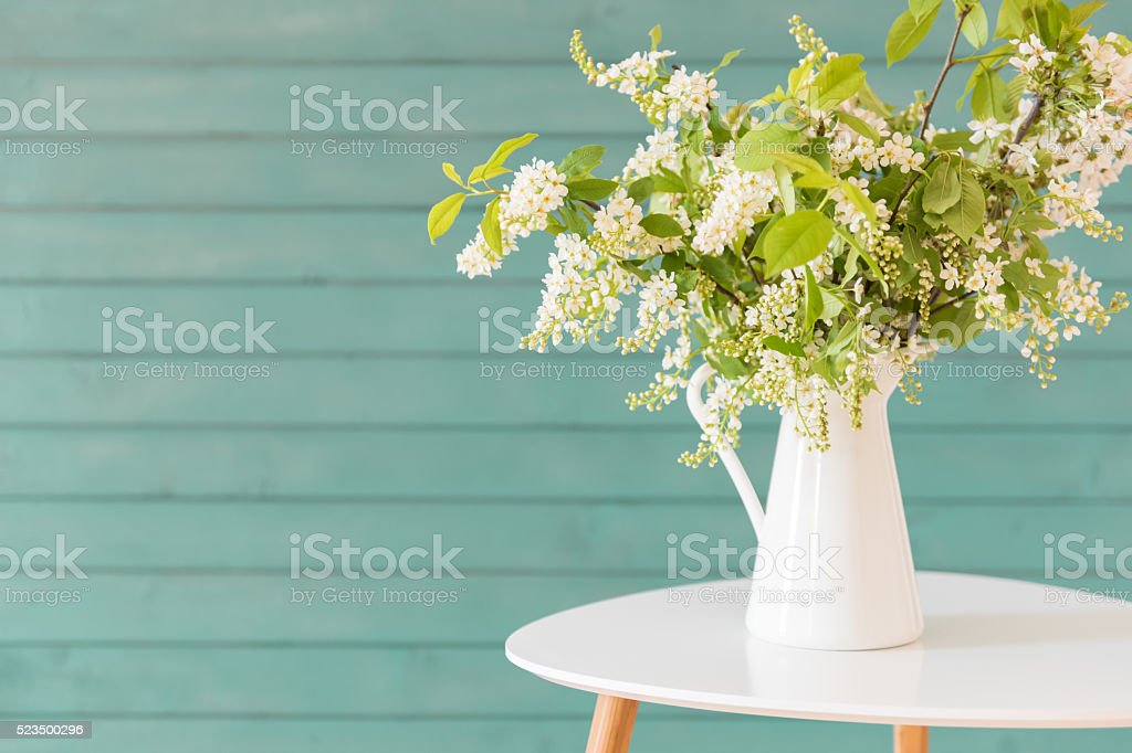 Beautiful white flowers in a vase, on blue wooden background stock photo